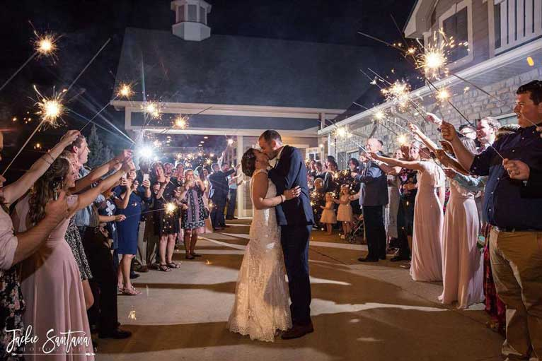 Newlyweds kiss under a sparkler exit after their wedding ceremony at The Ballroom at The Willows