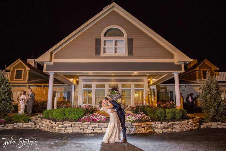 Bride and Groom kiss in front of their Indianapolis wedding reception venue, The Ballroom at The Willows