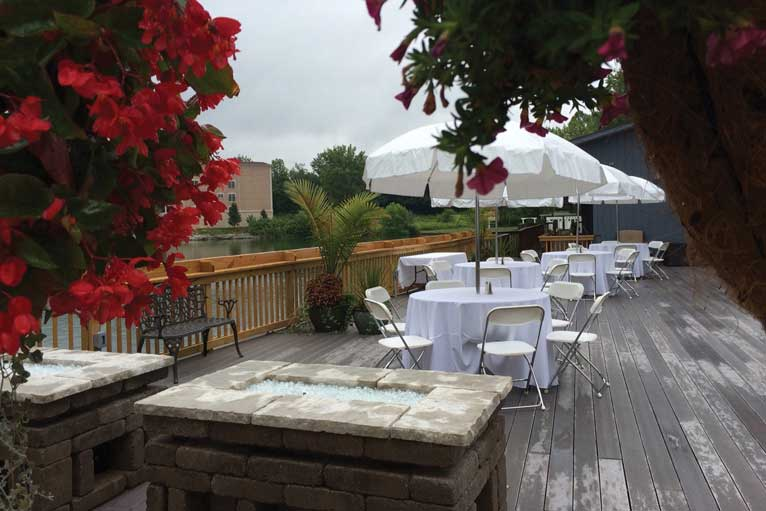 The outdoor patio at The Lodge at The Willows features a fire pit and a lakefront view in Indianapolis