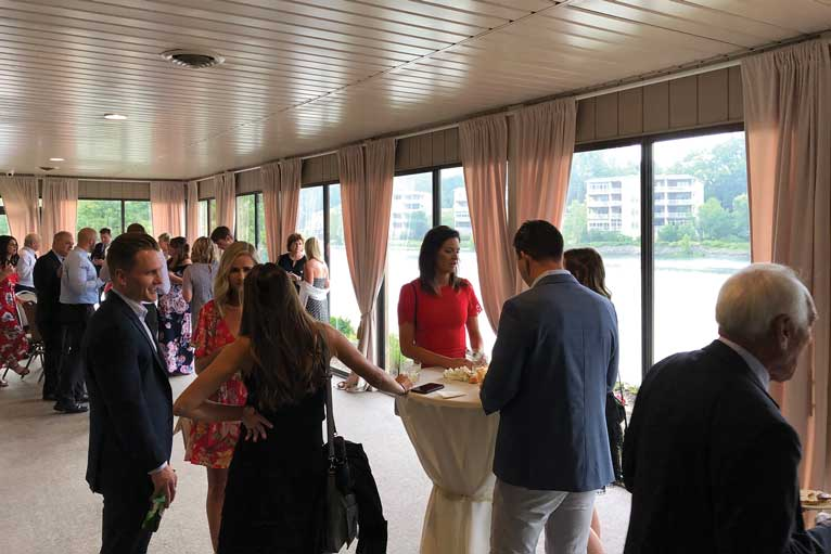 Wedding reception guests gather on the terrace at The Ballroom at The Willows for lakefront views