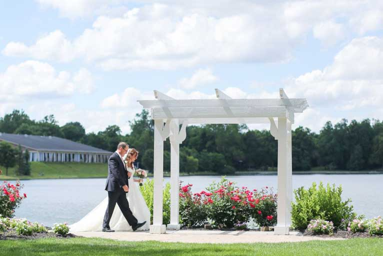 Father with bride about to walk down the aisle at an outdoor lakefront wedding ceremony at The Willows Event Center