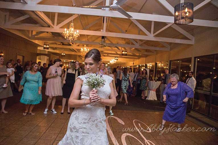 The bride preparing to throw the bouquet at a formal wedding reception at The Lodge at The Willows