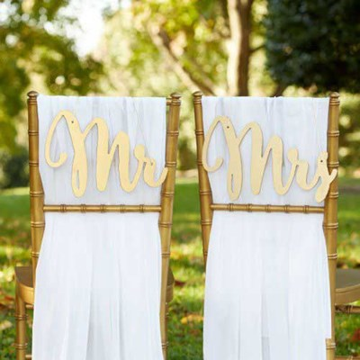 Mr. and Mrs. chair drapes make a cute addition to table decorations for any wedding reception