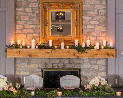 The fireplace mantel decorated for a wedding reception in The Lodge at The Willows