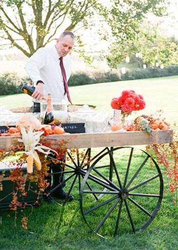 Outdoor wedding reception featuring a wagon cocktail cart complete the rustic theme