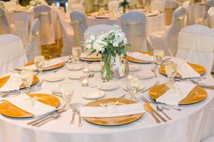 Wedding reception pre-set table featured white with gold accents at The Ballroom at The Willows