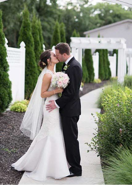 Newlyweds kiss in front of The Lodge at The Willows, their wedding reception venue in Indianapolis