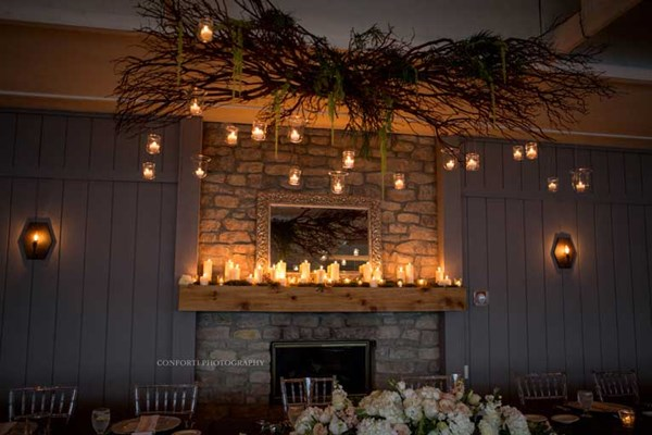 The fireplace for this wedding reception at The Lodge at The Willows is decorated with candles and string lights for a rustic theme