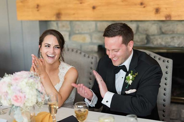 Bride and groom laugh at their rustic chic wedding reception at The Lodge at The Willows