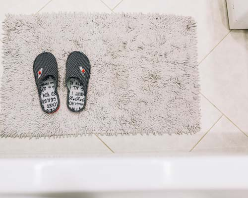 slippers on shaggy rug over bathroom floor tile (source: freepik.com)