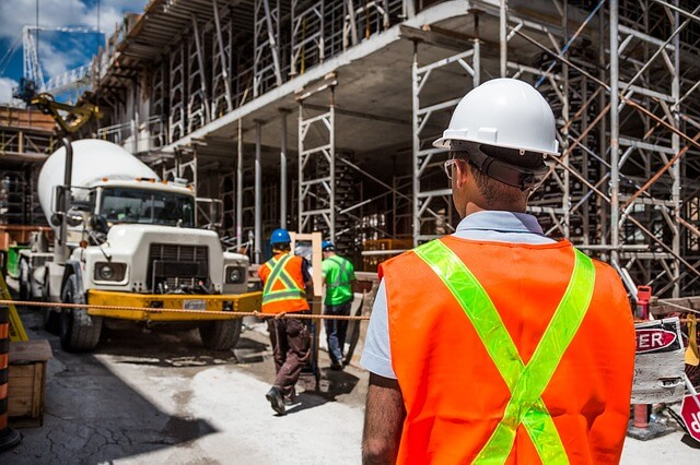 Image of a construction site with a construction manager overseeing site