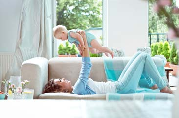 Mother holding her baby in the air in a new cleaned family room by Accent Maid Service in Indianapolis