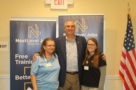 Indiana Governor, Eric Holcomb, in front of banners with NextLevel Jobs