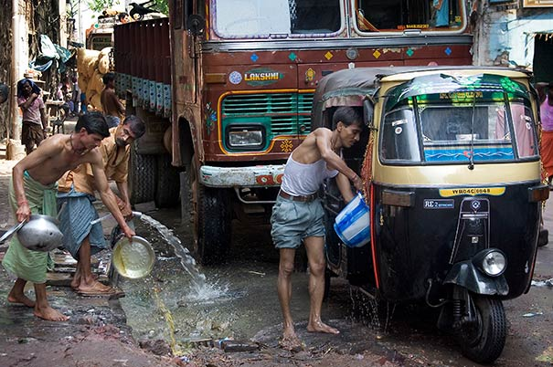 Men dumping gray water into street in India