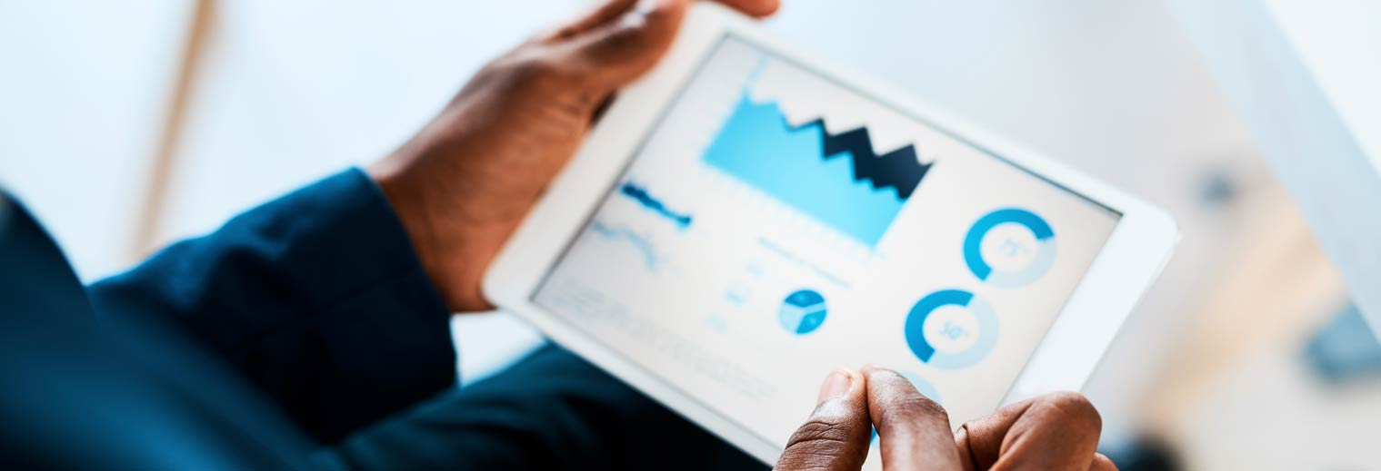 man looking at financial visualizations on tablet