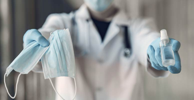 Doctor holding face mask and sanitizer to help prevent the spread of COVID-19 (source: freepik.com)