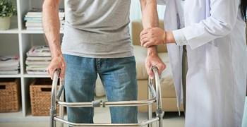 doctor helping male patient walk with walker (source: freepik.com)