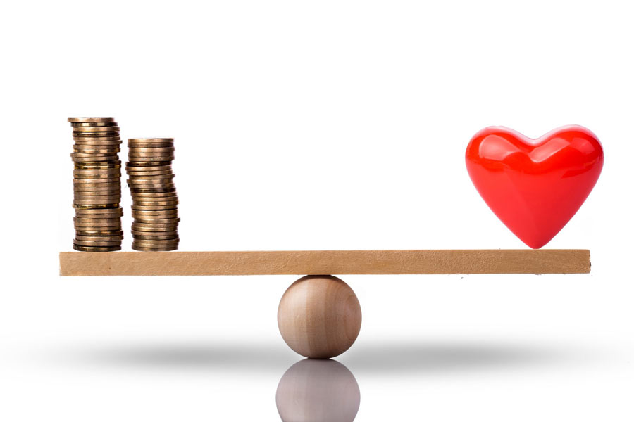 Heart and money (in coins) on a scale to represent balance